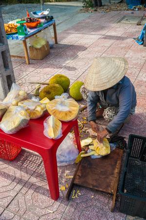 vendor: Vietnamese street vendor cuts and sells jet fruits Stock Photo