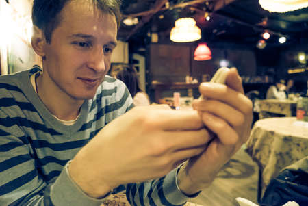 Man using a mobile phone in cafe photo