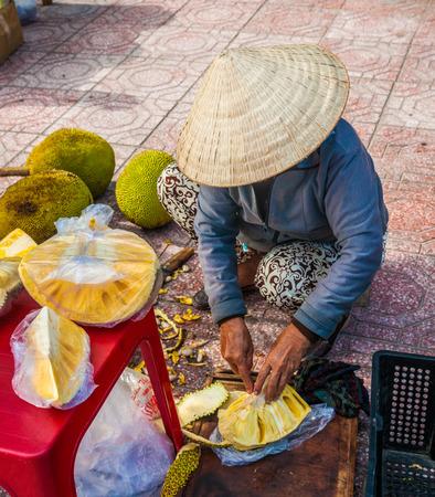 street vendor: Vietnamese street vendor cuts and sells jet fruits Editorial