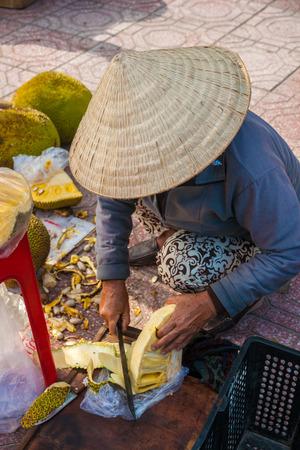 street vendor: Vietnamese street vendor cuts and sells jet fruits Stock Photo