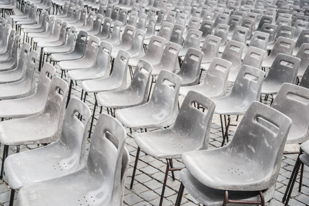 public address: Rows of empty plastic seats on stone pavement, outdoor setting