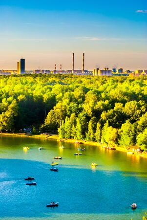 industrial park: City park, lake and forest with industrial landscape in distance Stock Photo