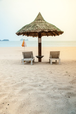 lounges: Two chaise lounges under a straw umbrella on a beach near the sea.  Stock Photo