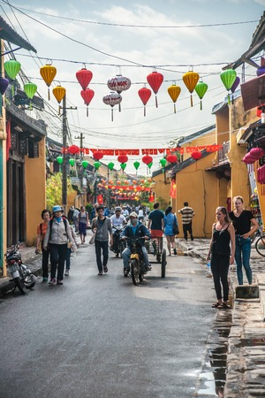 nang: HOI AN, VIET NAM - FEBRUARY 4, 2015: Unidentified tourists walking on a decorated street of Hoi An ancient city, Da Nang province, Vietnam. Hoi An is recognized as a World Heritage Site by UNESCO.