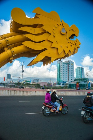 developement: DANANG CITY, VIETNAM - FEBRUARY 2, 2015 - Motorbikes on the The Dragon Bridge on February 2, 2015. The Bridge has recently received Engineering Exellence Award (EEA) in the USA