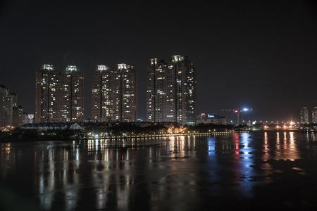 The landscape of Saigon: Cityscape của Hồ Chí Minh về đêm với ánh sáng rực rỡ của kiến trúc hiện đại, xem qua sông Sài Gòn ở miền Nam Việt Nam.