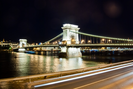 Chain Bridge in Hungary Budapest. Image of night city with night traffic and reflections in the water of Danube river photo