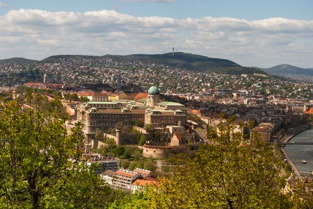 buda: Cityscape of Budapest in warm sunlight with Buda Castle visible through trees of Gellert Hill. Stock Photo