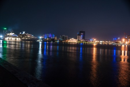 The landscape of Saigon: Cityscape of Ho Chi Minh at night with bright illumination of modern architecture, viewed over Saigon river in Southern Vietnam.
