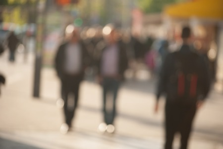 no people: People walking down the street in the evening, beautiful light at sunset. The photo is purposely made out of focus, no faces are recognisible Stock Photo