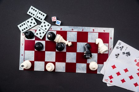 Various board games and figurines over checkers board and dark background. Metaphor for gaming and gambling. Stock Photo