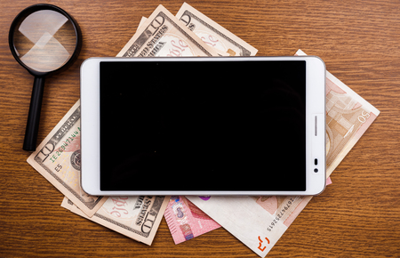 money online: Mobile device concept background with tablet pc on wood. App analytics, make money online, gadget security and blogging topics.