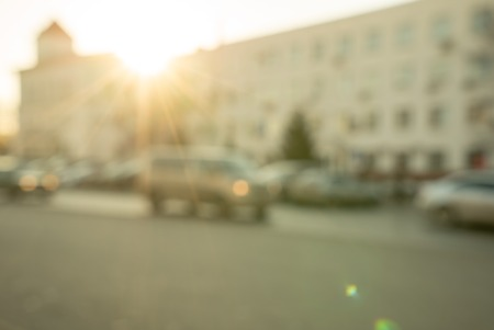 lit image: Traffic at sunset, defocused image of a road lit with warm light of setting sun