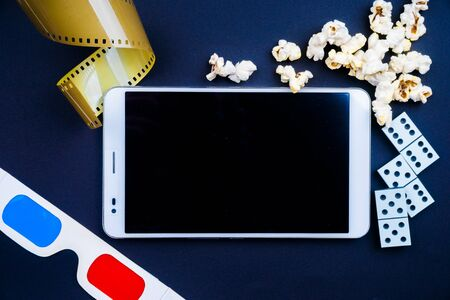 table games: Tablet pc with cinema glasses and table games on dark background