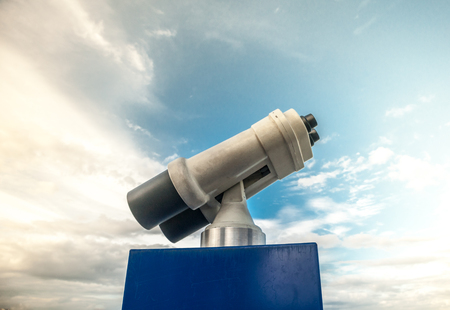 sky metaphor: Tower viewer against blue cloudy sky. Vivid photography of sightseeing binocular as a metaphor for touristic destinations, forecasting or planning and business analysis.