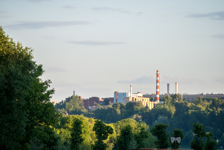 urbanism: Powerplant seen in distance surrounded by nature. Symbol of Technology, pollution and urbanism