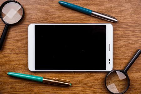 seguridad social: Gadget en el escritorio de madera - concepto de an�lisis de aplicaciones, la investigaci�n en l�nea y b�squeda en la web. Fondo para la publicidad y los blogs. Foto de archivo