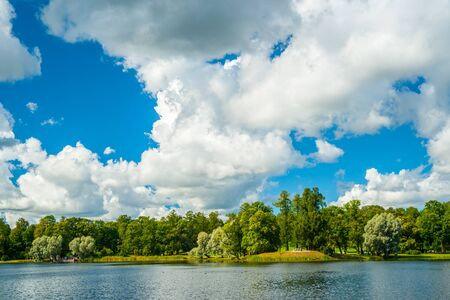 green hills: Beautiful landscape in Tsarskoye selo near Saint-Petersburg, Russia. Russian nature with the lake and green trees under blue cloudy skies in summertime. Bright seasonal image - perfect as background.