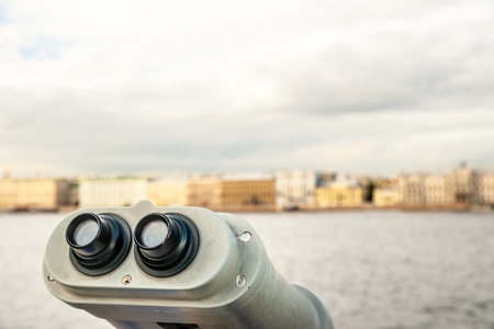 viewer: Tower viewer turned towards Neva river in Saint-Petersbourg, Russia. Tourist destionations image. Sightseeing binocular against blurred background of city at dawn in light of sunset. Stock Photo