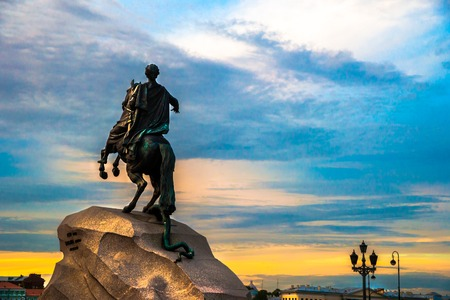 uomo a cavallo: The Bronze Horseman - equestrian statue of Peter the Great in Staint-Petersburg, Russia. One of the major tourist attractions viewed in the direction of Neva river against beautiful sky at sunset. Archivio Fotografico
