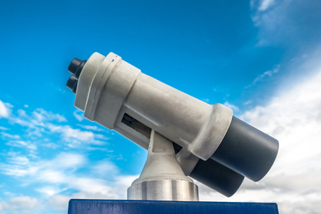 foresee: Tower viewer against blue cloudy sky. Vivid photography of sightseeing binocular as a metaphor for touristic destinations, forecasting or planning and business analysis.