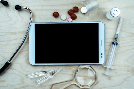 Tablet pc with medical objects on a desk as a metaphor for electronic diagnostic or healthcare mobile apps. Medical background Stock Photo