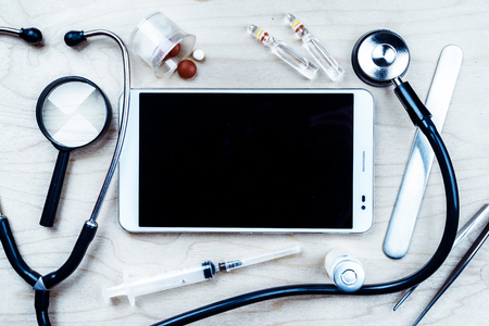 health technology: Tablet pc with medical objects on a desk as a metaphor for electronic diagnostic or healthcare mobile apps. Medical background Stock Photo