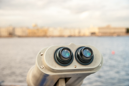 Tower viewer turned towards Neva river in Saint-Petersbourg, Russia. Tourist destionations image. Sightseeing binocular against blurred background of city at dawn in light of sunset. Stock Photo