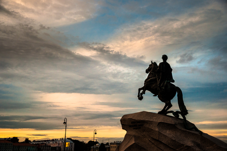 The Bronze Horseman - equestrian statue of Peter the Great in Staint-Petersburg, Russia. One of the major tourist attractions viewed in the direction of Neva river against beautiful sky at sunset. Stock Photo