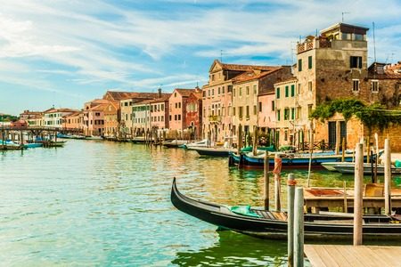 forefront: Beautiful colorful image of a canal in Venice with moorings and a gondola in the forefront and old houses under blue cloudy sky in the background.