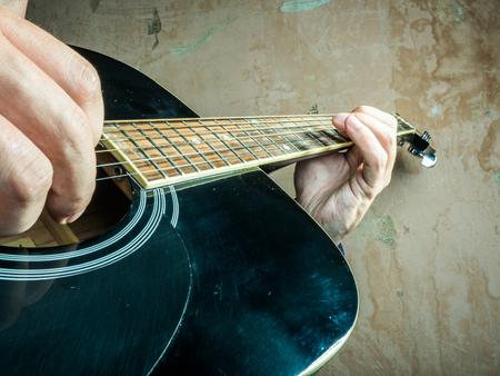 fingertips: Closeup photo of an acoustic guitar played by a man. Only hands visible. Unrecognizible guitar player. Stock Photo