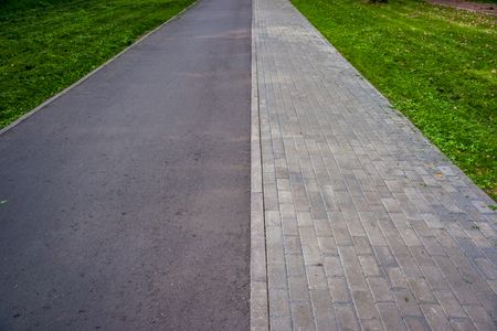 road and path through: Pathway in the park paved with tile and partly asphalted with green grass around
