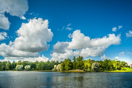 Beautiful russian landscape with willows near water of a lake and clouds in blue sky. Catherine park in Pushkin - Tsarskoe Selo, St.Petersburg, Russia.