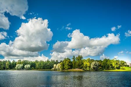 Mooie Russische landschap met wilgen in de buurt van het water van een meer en wolken in blauwe hemel. Het park van Catherine in Poesjkin - Tsarskoe Selo, St. Petersburg, Rusland. Stockfoto