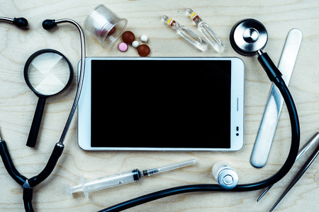 stethescope: Tablet pc with medical objects on a desk as a metaphor for electronic diagnostic or healthcare mobile apps. Medical background Stock Photo