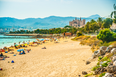 View of the beach of Palma de Mallorca with people lying on sand and the gorgeous cathedral building visible in background. Palma-de-Mallorca, Balearic islands, Spain. Banque d'images
