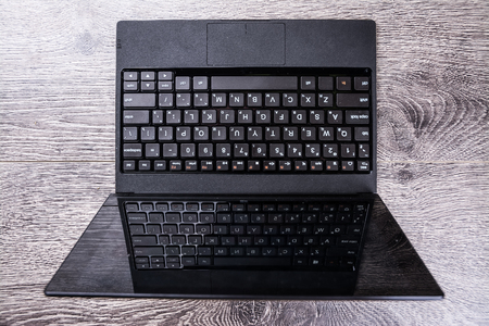viewed: Black laptop on wood viewed from above.