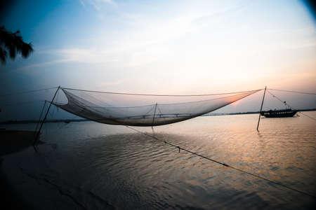 purple sunset: Calm scene of fishing net against purple sunset. Nautical background.