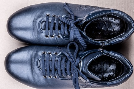solid blue background: Mens shoes for autumn on light solid background. Blue boots on the ground. Stock Photo