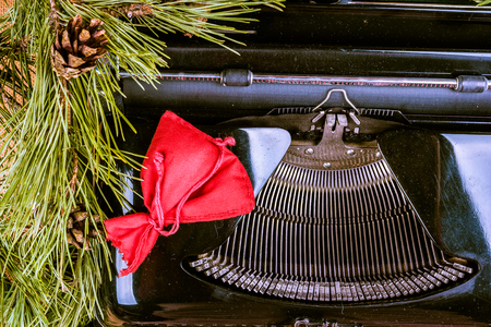 writing activity: Vintage typewriter with Christmas tree fur. Photography for blog and creative banners, or hero image. Symbol of blogging, writing, internet activity and creativity.