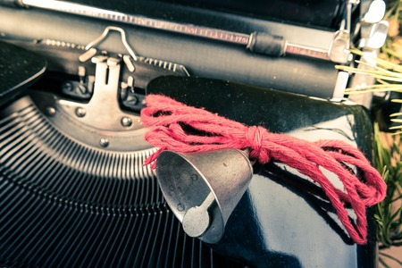 writing activity: Vintage typewriter with red Christmas tree decoration. Photography for blog and creative banners, or hero image. Symbol of blogging, writing, internet activity and productivity.