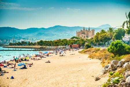 Uitzicht op het strand van Palma de Mallorca met mensen liggend op het zand en de prachtige kathedraal gebouw zichtbaar in de achtergrond. Palma-de-Mallorca, Balearen, Spanje.