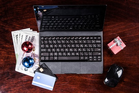 electronic banking: Black laptop on wood with christmas decoration and giftboxes and bank card viewed from above. Image for internet shopping, electronic banking and web payment.