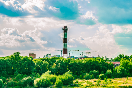 tall chimney: Chimney of a factory and construction site with cranes behind green trees. Industrial landscape with clouds in the sky and greenery. Stock Photo