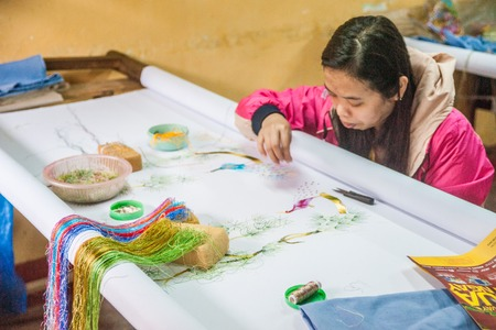po: HOI AN, VIETNAM - FEBRUARY 5, 2015: Vietnamese woman produces hand-made embroidery, in Hoi An, Feb 5, 2015.