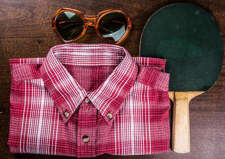 ping pong: Vintage paleta de ping pong con la camisa retro y gafas de sol en el fondo de madera. S�mbolo de las vacaciones de verano y recreaci�n. Antecedentes de deportes de verano.