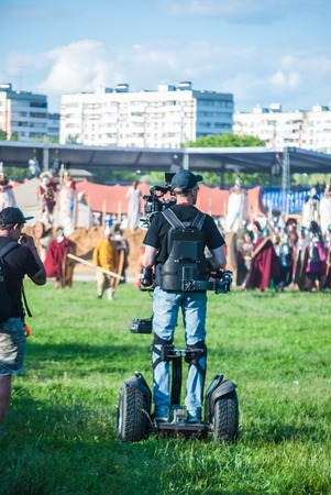 easy way: MOSCOW - JUNE 06, 2015: Cameraman on Steadiseg shooting historical reenactment in Kolomenskoye, Moscow. Steadiseg is easy way to capture smooth tracking shots at a fairly brisk pace. Editorial