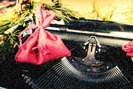 writing activity: Vintage typewriter with red Christmas tree decoration. Photography for blog and creative banners, or hero image. Symbol of blogging, writing, internet activity and creativity. Stock Photo