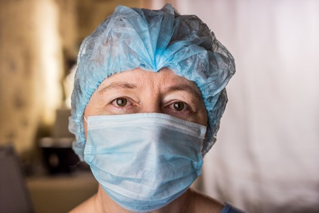 surgical cap: Closeup of female doctor wearing medical mask and surgical cap looking seriously and worried at patient Stock Photo