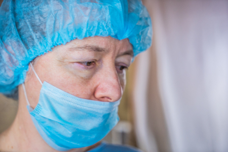 Closeup of female doctor wearing medical mask and surgical cap looking seriously and worried at patient Stock Photo